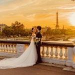 Couple de mariés sur pont devant la tour Eiffel